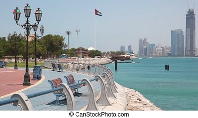 sea shore with flag of United Arab Emirates, skyscrapers on...