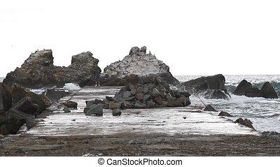 Sea splashing against rocks and pier