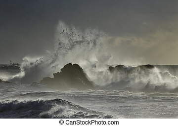 Sea spray at sunset. Northern portuguese rocky coast.