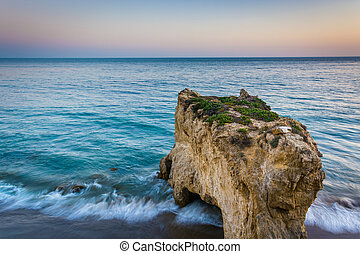 Sea stack and waves in the Pacific Ocean at sunset, seen from a