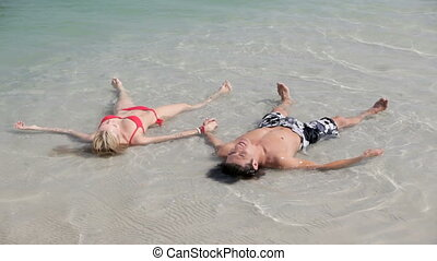 Sea stars - Young man and woman lying in water like sea ...