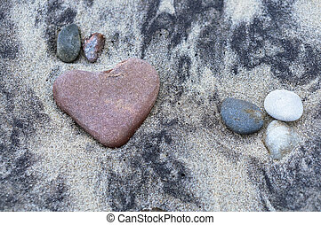 sea stone in the shape of a heart on the sand, red stone ...