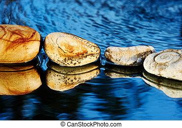 Sea stones on dark blue - Four stones on dark blue ...