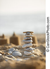 sea stones tower on sand. summer and sunset on sea background. relaxation and meditation on beach