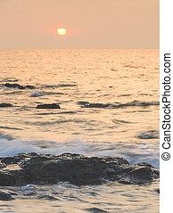 Sea sunrise with rock on beach