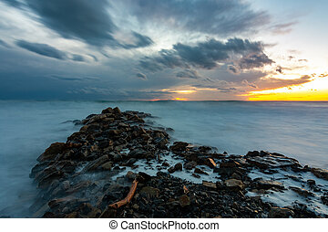 Sea sunset after sunset, in the foreground a breakwater of stones