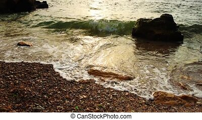 Sea surf at the coast, sunny water with white foam splashing...