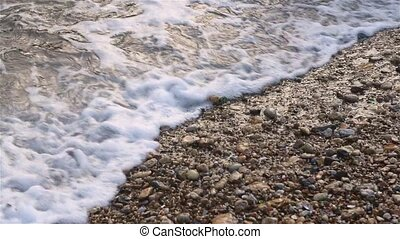 Sea surf at the coast, water with white foam splashing to...