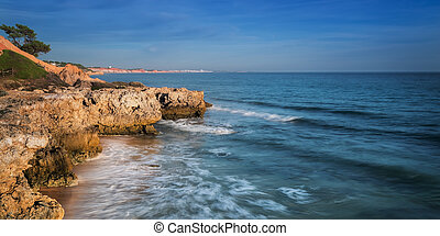 Sea surf in Albufeira beach and mountain in Portugal. ...