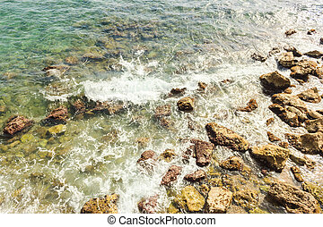 Sea surf in the Mediterranean. Wet stones and waves