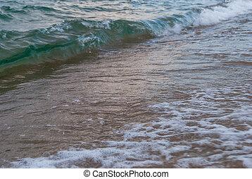 sea surf on a sandy beach on the coast in Greece
