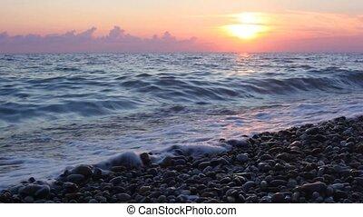 sea surf on pebble beach, sunset sky above waving sea in...