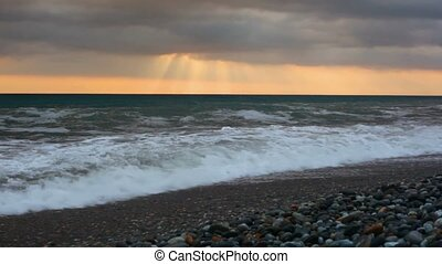 sea surf on pebble beach under sunset sky with rain clouds