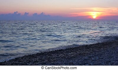 sea surf on pebble coast, sunset sky above waving sea in background