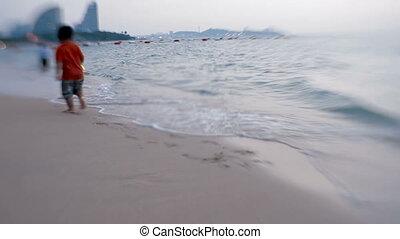 Sea surf. Waves erase kid's footprints on the sand. Pattaya,...