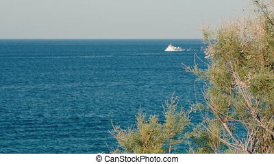 Sea view. Panorama of sea and sky. Lonely cargo ship in the distance. Concrete sea strengthening.