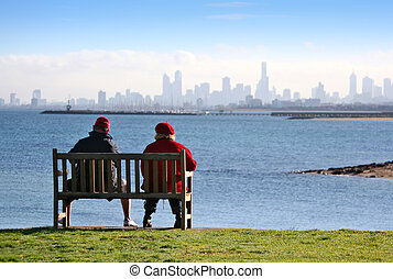 Sea View - A man and woman on a clifftop bench enjoy the...