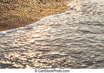 Sea wave on sand and stone at sunrise