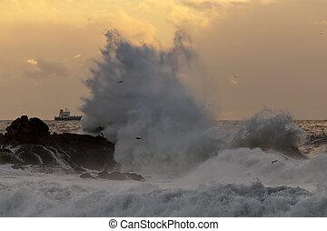Sea wave splash at sunset