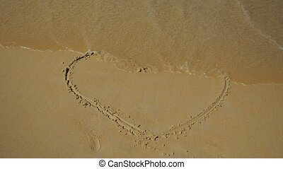 Sea wave washes a painted heart on the sand. Slow motion