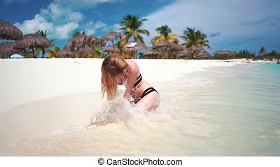 Sea wave wets Woman sitting on the beach. Caribbean Sea.