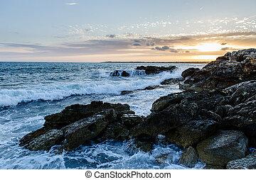 Sea waves and rocks at sunset