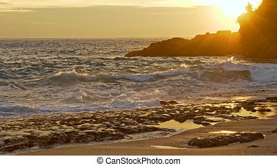 Sea waves and rocky shore at sunset