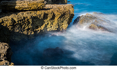 Sea waves are beating against the rocky shore