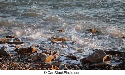Sea waves are fighting against the rocks on the shore.