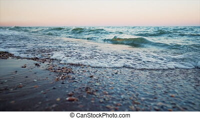 Sea waves at sunset. Beautiful stormy weather on sandy beach. Camera shoots as close to water as possible. Breathtaking sight. Slow motion. High quality FullHD footage
