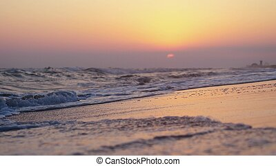 Sea waves at the beach at purple sunset