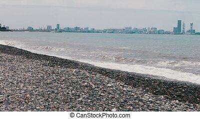 Sea waves beat on stony shore on the embankment of the Georgian city resort of Batumi