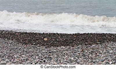 Sea waves beat on stony shore on the embankment of the Georgian city of the resort of Batumi