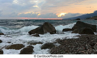 Sea waves break about big stones ashore at sunrise