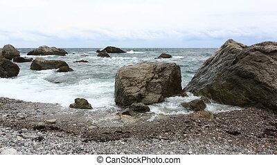 Sea waves break about big stones near the seashore
