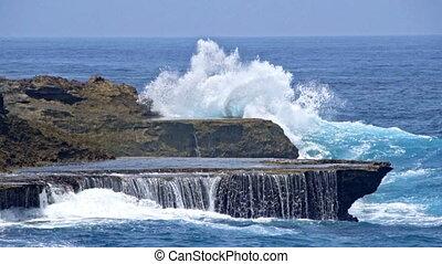 Sea waves break of the rocky shore slow motion