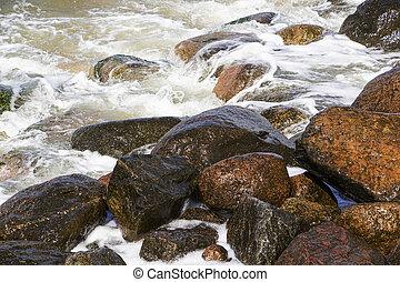 sea waves break on the rocks, a lot of spray. Sunny day.