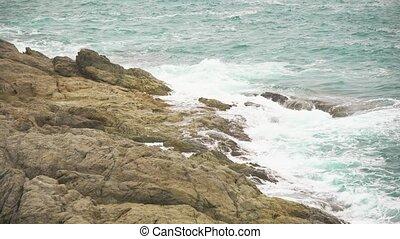 sea waves break on the rocky shore. foaming water, the restless sea
