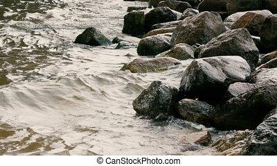 Sea waves break up on the rocks,