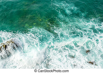 Sea waves break up on the stones of the coast. The raging sea and foam. View from above. Green background.