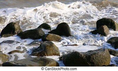 sea waves breaking on coastal stones, Caspian Sea, Iran.