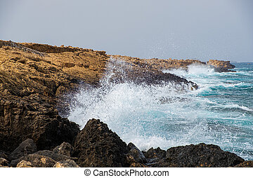 Sea waves crash onto rocks at Apostolos Andreas beach in...