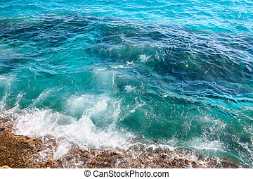 Sea waves crashing against the rocks, view from above. Mediterranean sea.
