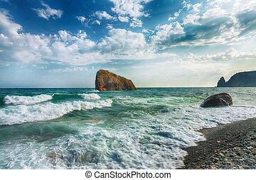 Sea waves crashing on the shore and flowing above seashore pebbles.
