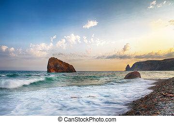 Sea waves crashing on the shore and flowing above seashore pebbles