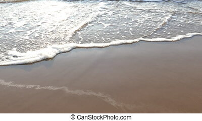 Sea waves forming white foam on the sandy beach - Closeup...