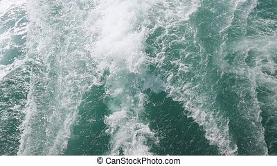 Sea waves from a boat a huge stream of deep blue water with white foam rising up. slow motion.