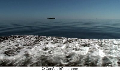 Sea waves from ship on water surface in ocean.
