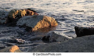 Sea waves gently hitting stones at the beach during sunset. Golden hour time.