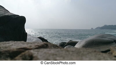 Sea waves hitting rocks on the beach in Phuket
